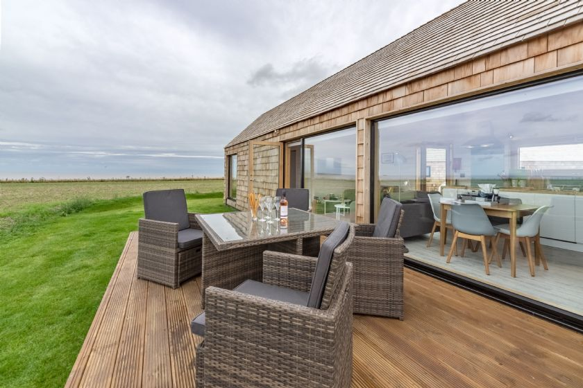 Decked terrace with garden furniture.