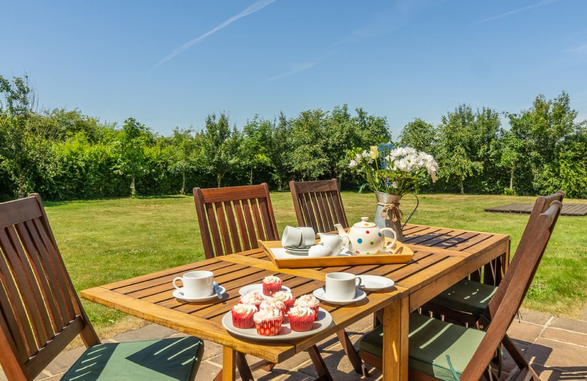 Large fully enclosed lawned garden, ideal for children to play ball games together with an outdoor dining area with barbecue overlooking open farmland