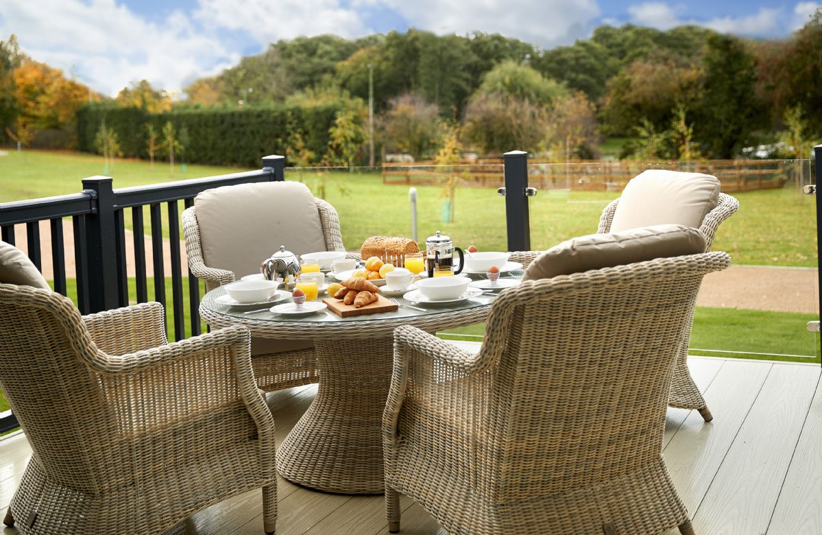 Large, partly covered decking area with three piece rattan suite and table and chairs