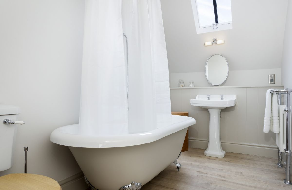First floor: En-suite bathroom with roll-top bath and shower over