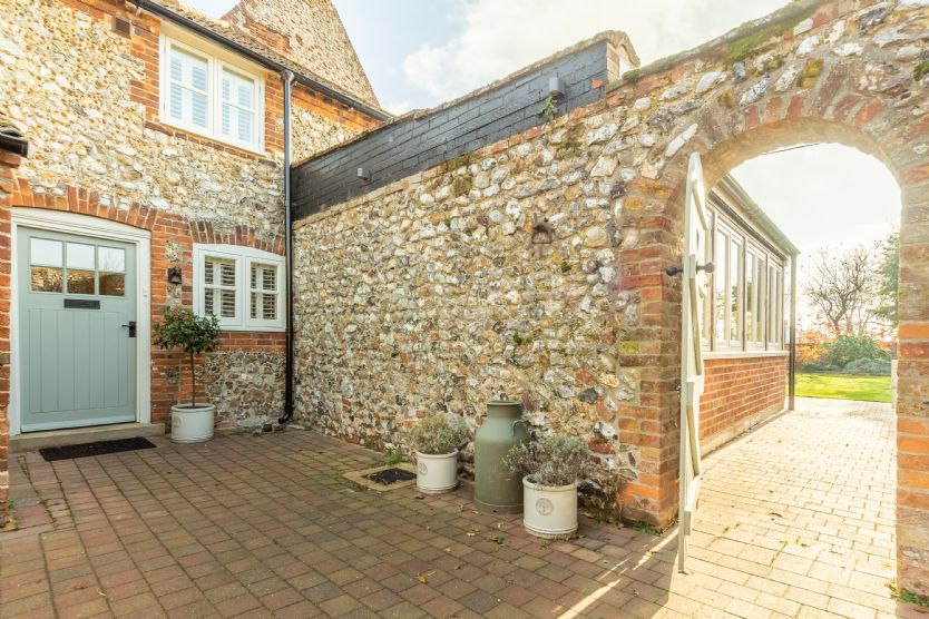 Feature brick wall arch leads into the fully-enclosed walled rear garden