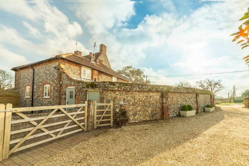 This attractive brick and flint semi-detached property is approached via a shingle driveway, with parking for two cars inside the gate and one car outside