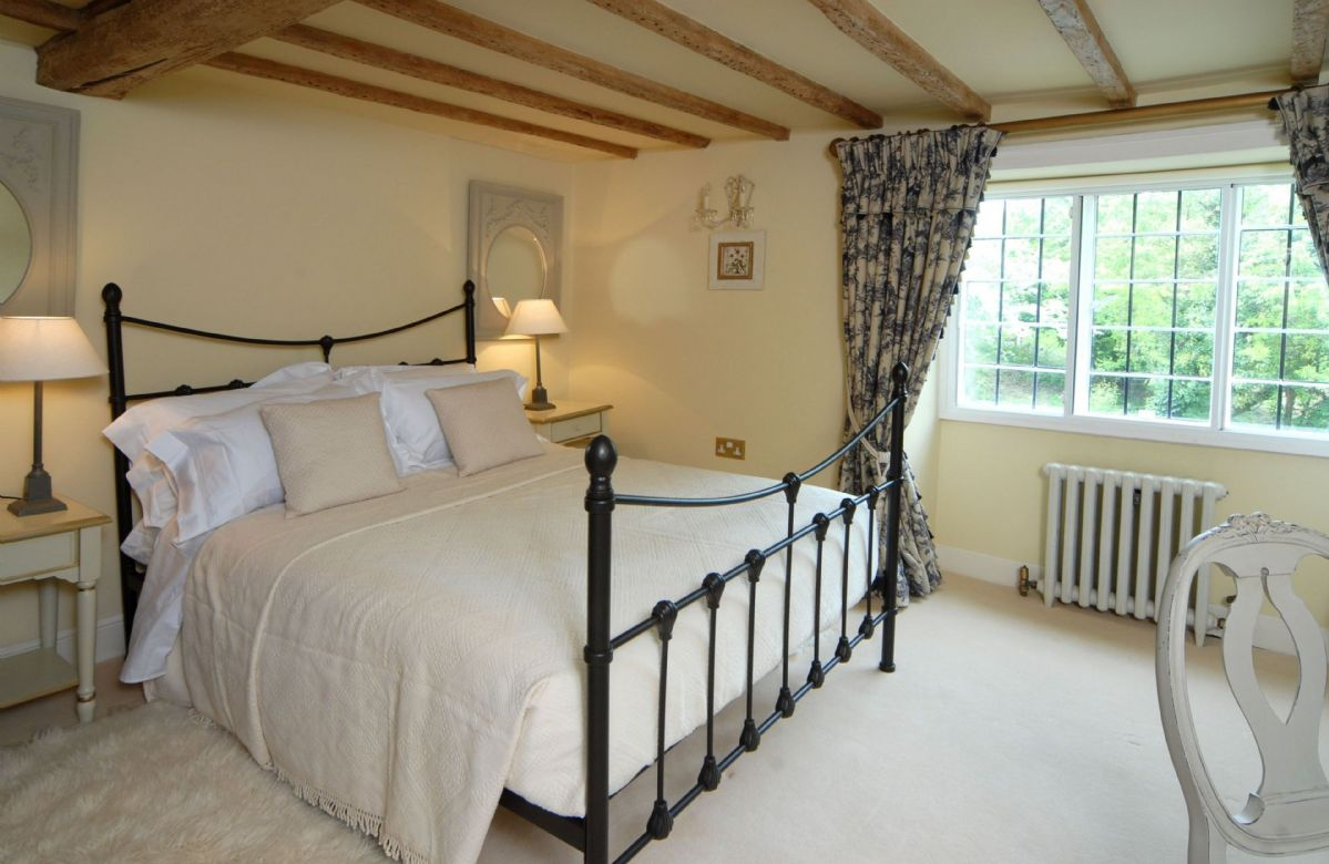 First floor:  Bedroom two with antique, wrought iron bed