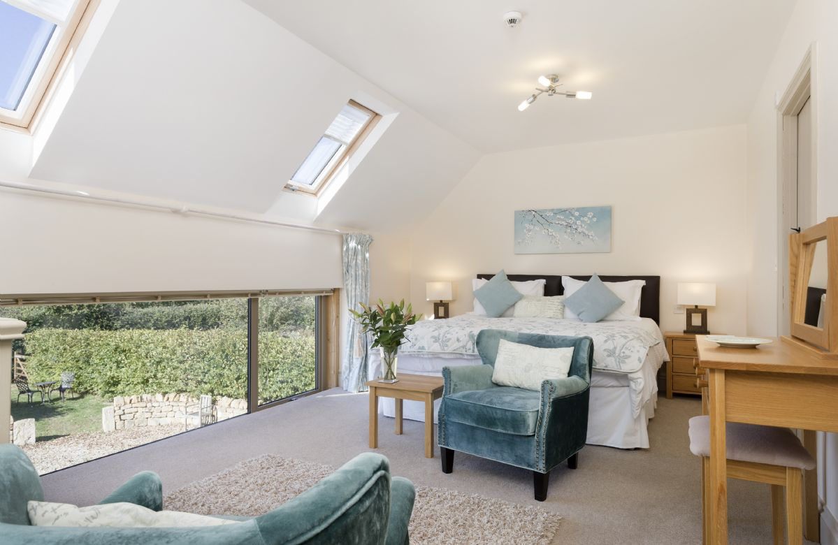 The Byre: First floor bedroom with 6' super king bed, seating area and en-suite bathroom
