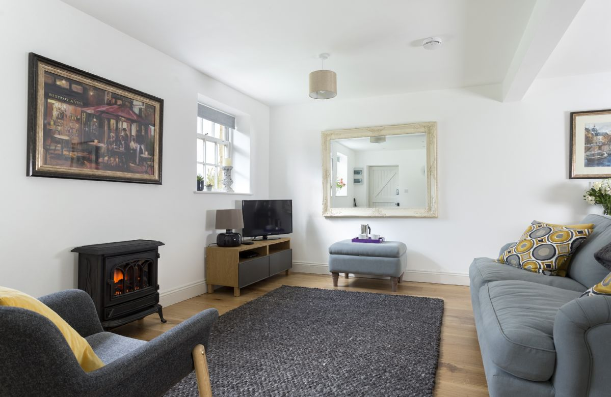 Ground floor: Sitting area with television and woodburner style electric heater