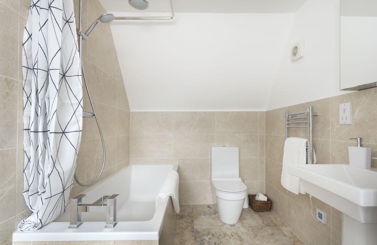 First floor: En-suite bathroom with bath and shower over