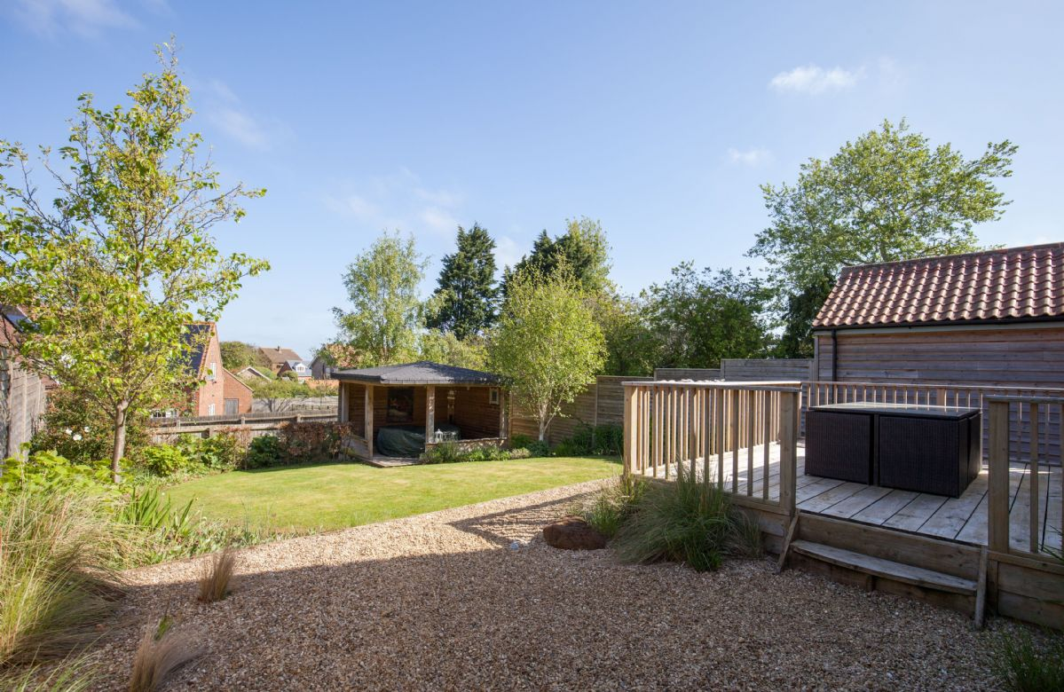 To the rear is a lovely sun trap deck accessed from the dining area and a fully enclosed lawned garden