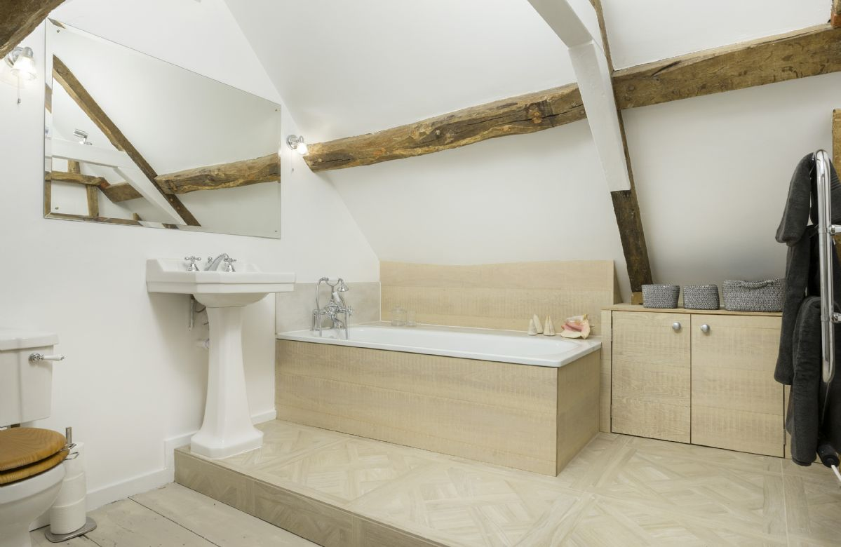 Second floor: En-suite bathroom with bath and handheld shower attachment