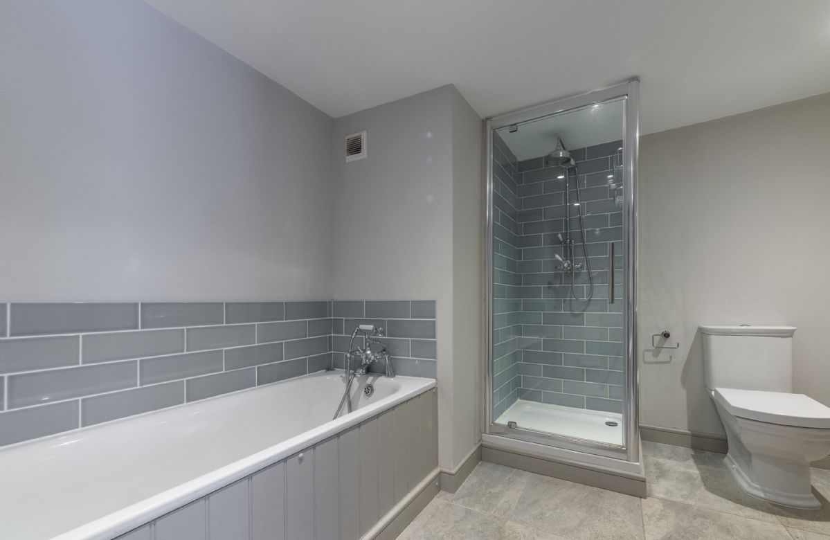 First floor: Family bathroom with bath with hand-held shower attachment and separate shower cubicle