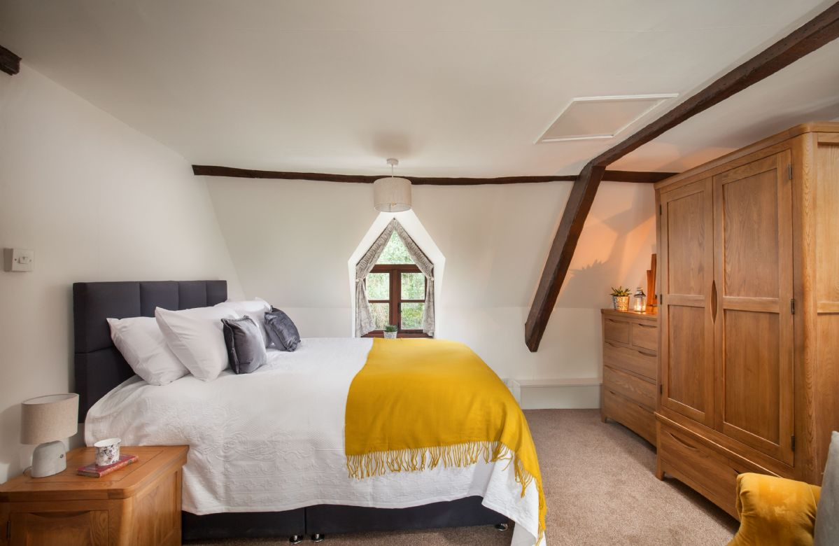 First floor: Master bedroom with traditional beams and feature window