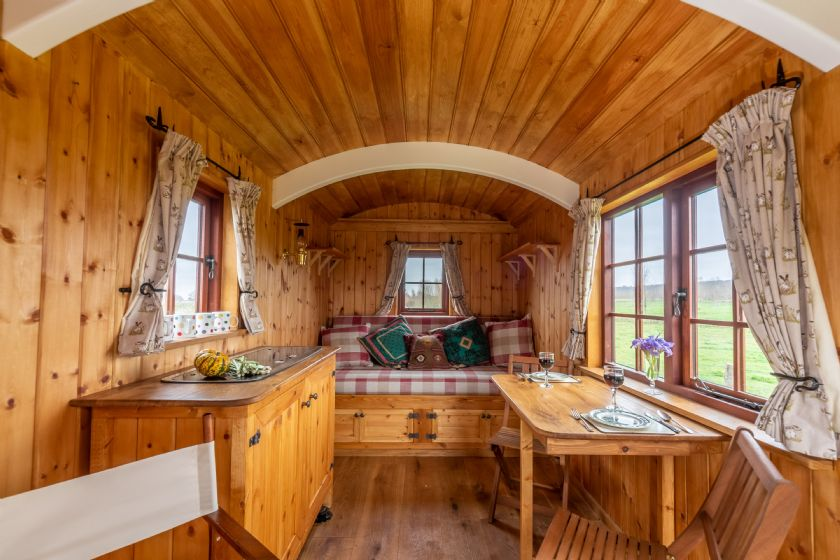 Interior of Shepherd's Hut with cooking and dining area with sofa