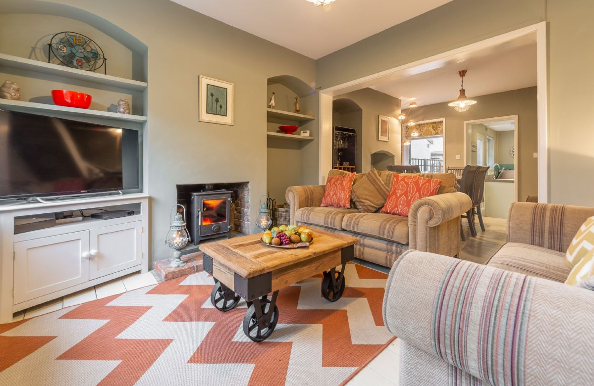 Ground floor: Cosy sitting room which has two large sofas and a wood burning stove, large flat screen television