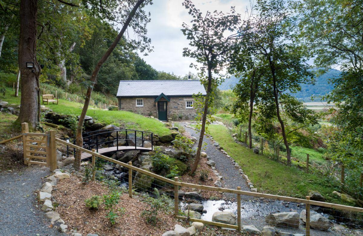 This detached cottage lies on its own off a woodland track with a pretty stream tumbling past