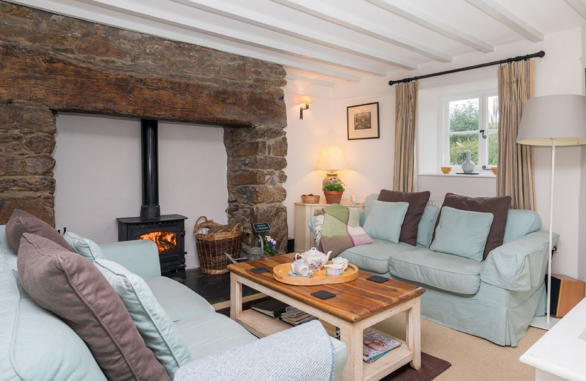 Ground floor:  Sitting room with beamed fireplace and multi fuel burning stove