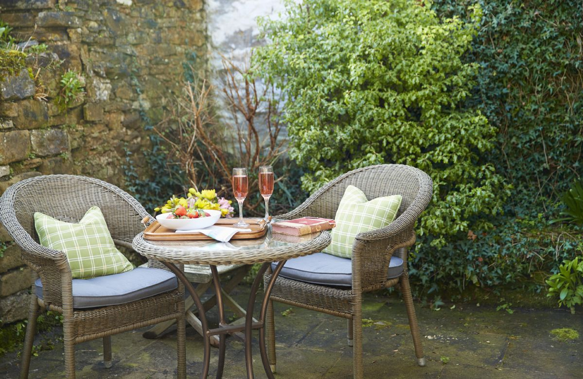Sunny private patio with seating fro two to the rear of the cottage