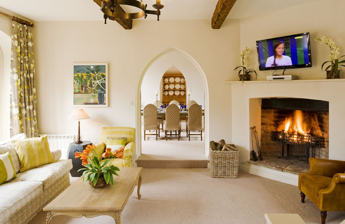 Ground floor: The large, dramatic sitting room with its original beams has two seating areas, with comfortable sofas and chairs and a wood-burning stove