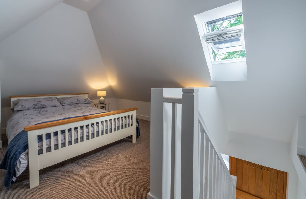 First floor: Spacious loft bedroom with double bed and veux window