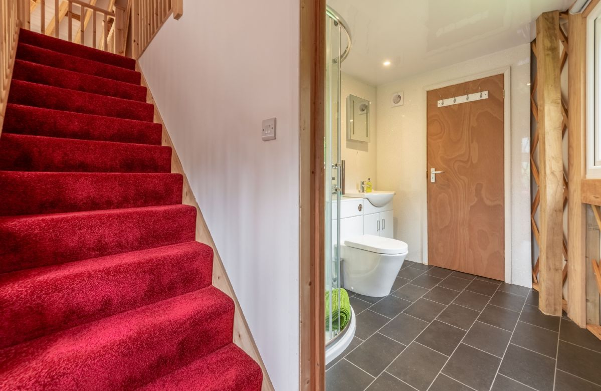 Ground floor: Stairway leading up to upper mezzanine level and downstairs bathroom