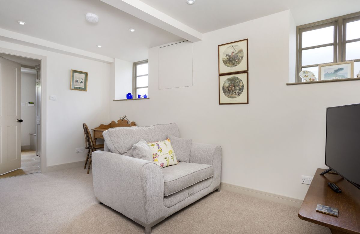 Ground floor: Cosy snug area with sofa, desk and chair