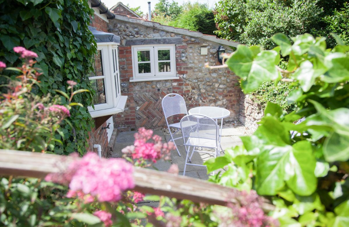 To the rear of the cottage is a quaint courtyard seating area with a table and chairs, perfect for your early morning breakfast