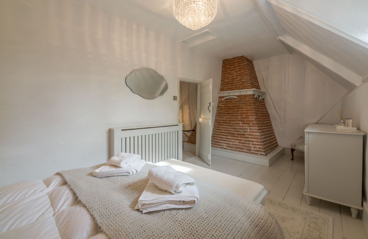 First floor: The main bedroom features a brick chimney and is large enough to accommodate a travel cot