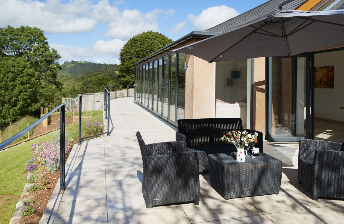 A staggering 16 metres of bi-fold doors opening out to a tiled balcony overlooking the beautiful river