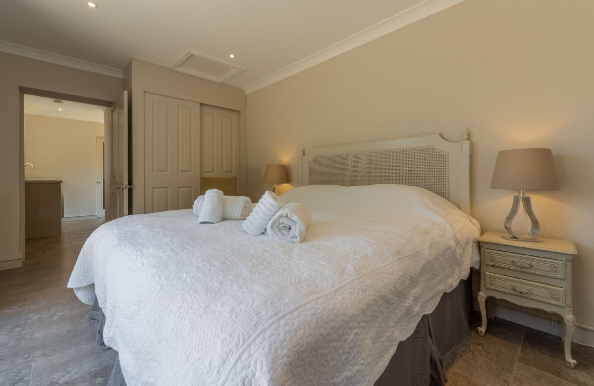 Ground floor: Large bedroom with king size bed and french doors leading out to courtyard