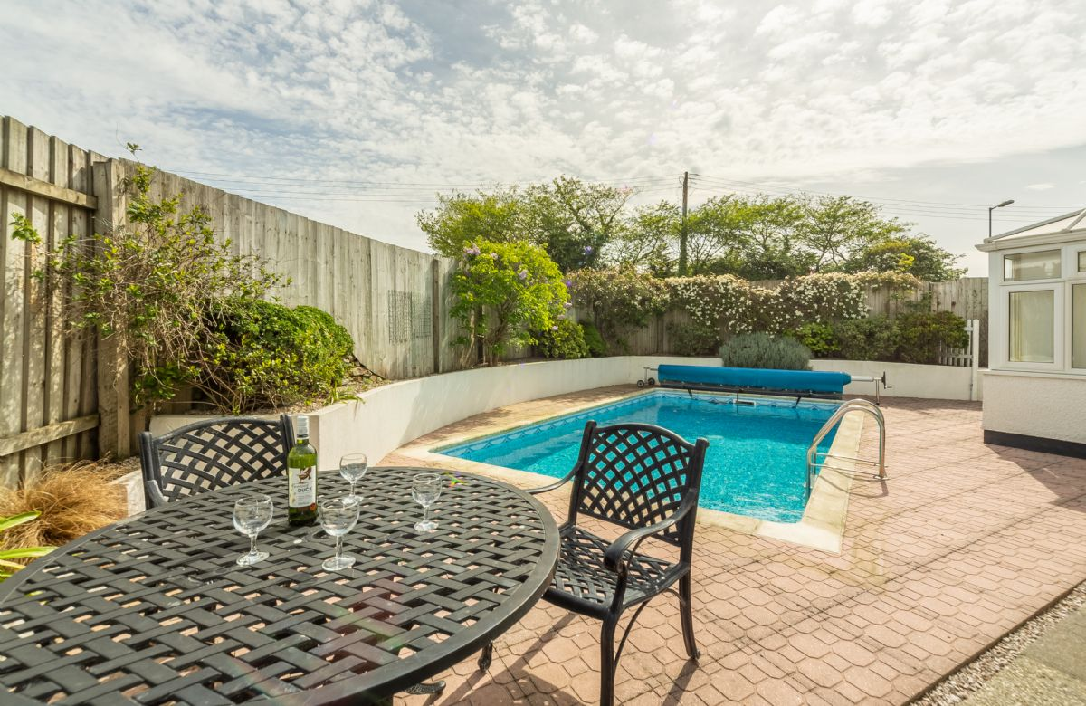 Pool terrace with garden furniture and charcoal barbecue