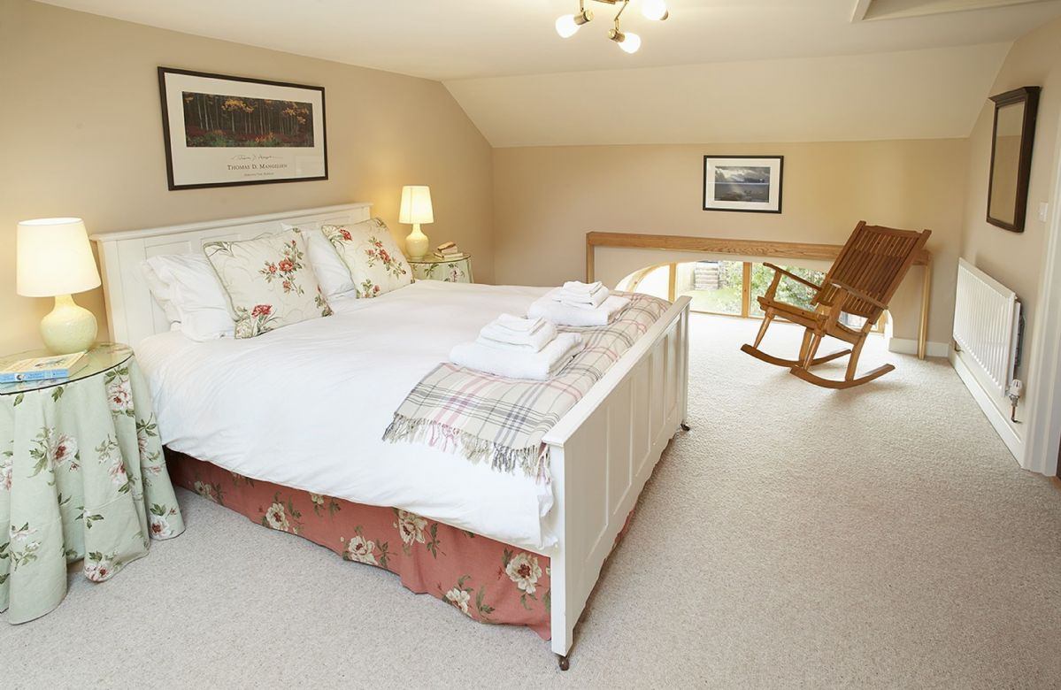First floor: Double bedroom with 5' king size bed and an antique linen fold carved bed