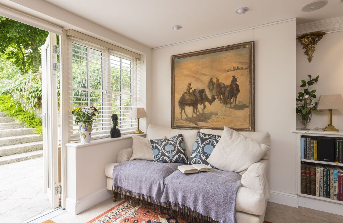 Ground floor:  The dual aspect sitting room leads out to the charming terrace