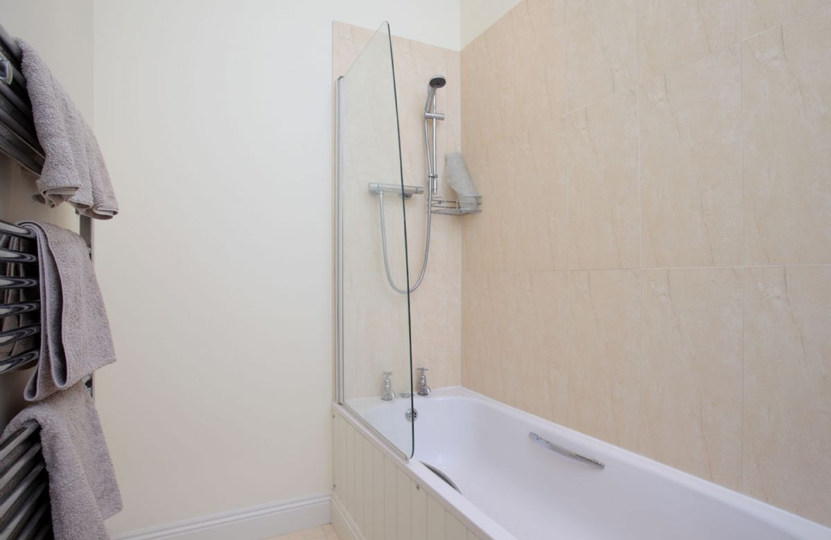 Upper ground floor: En-suite bathroom with bath and shower over
