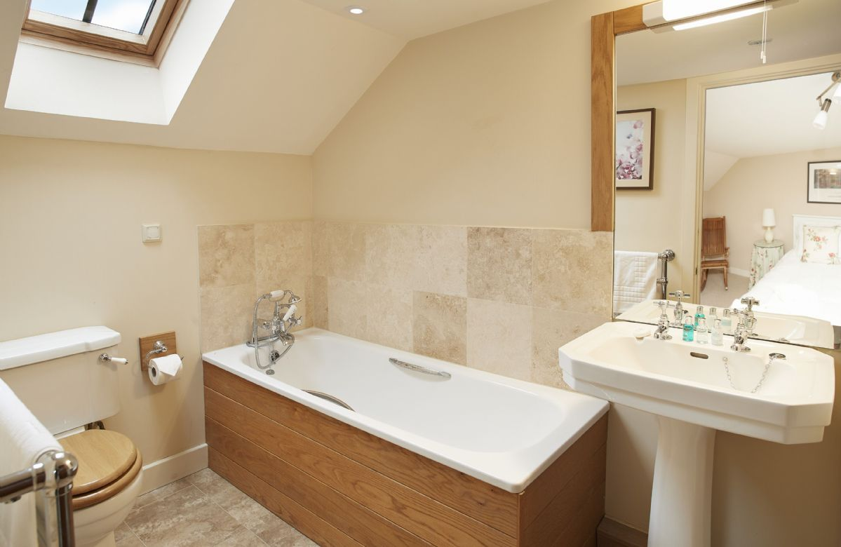 First floor: En-suite bathroom with bath and shower on riser