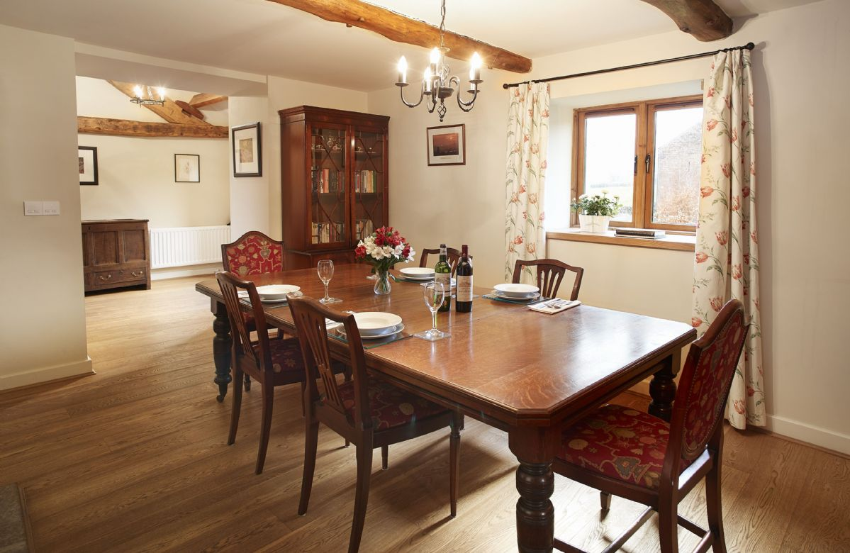 Ground floor: Dining room with table seating six guests and double sided cast iron fireplace