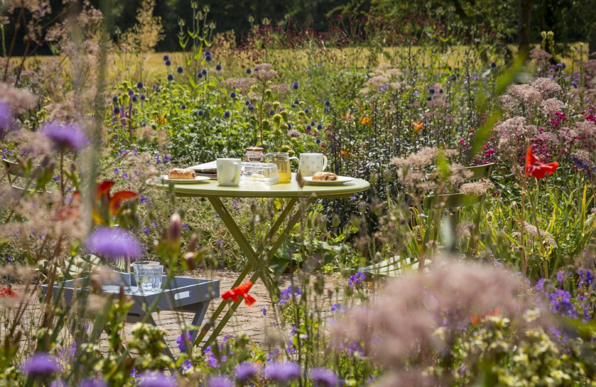 Delightful bistro table and chairs amongst the wildflower garden