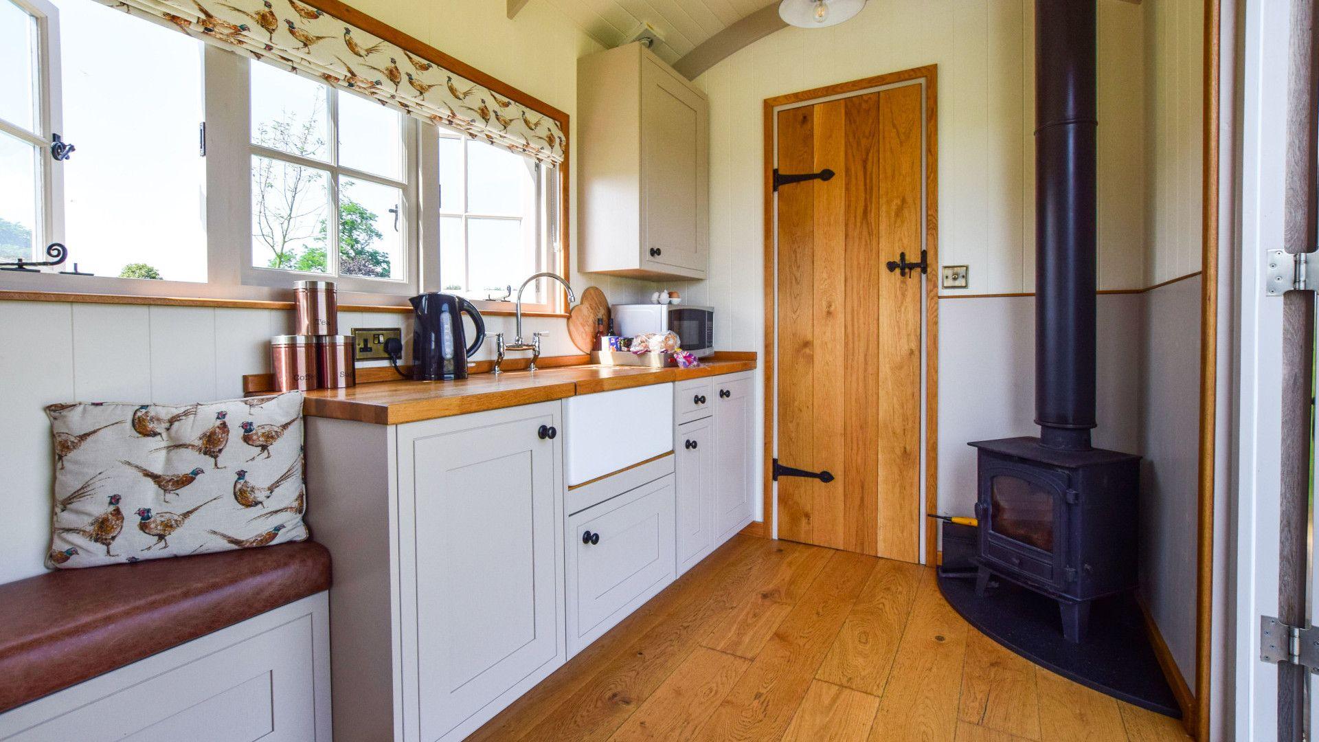 Living area with wood burner, Shepherds Hut at Avon Farm, Bolthole Retreats