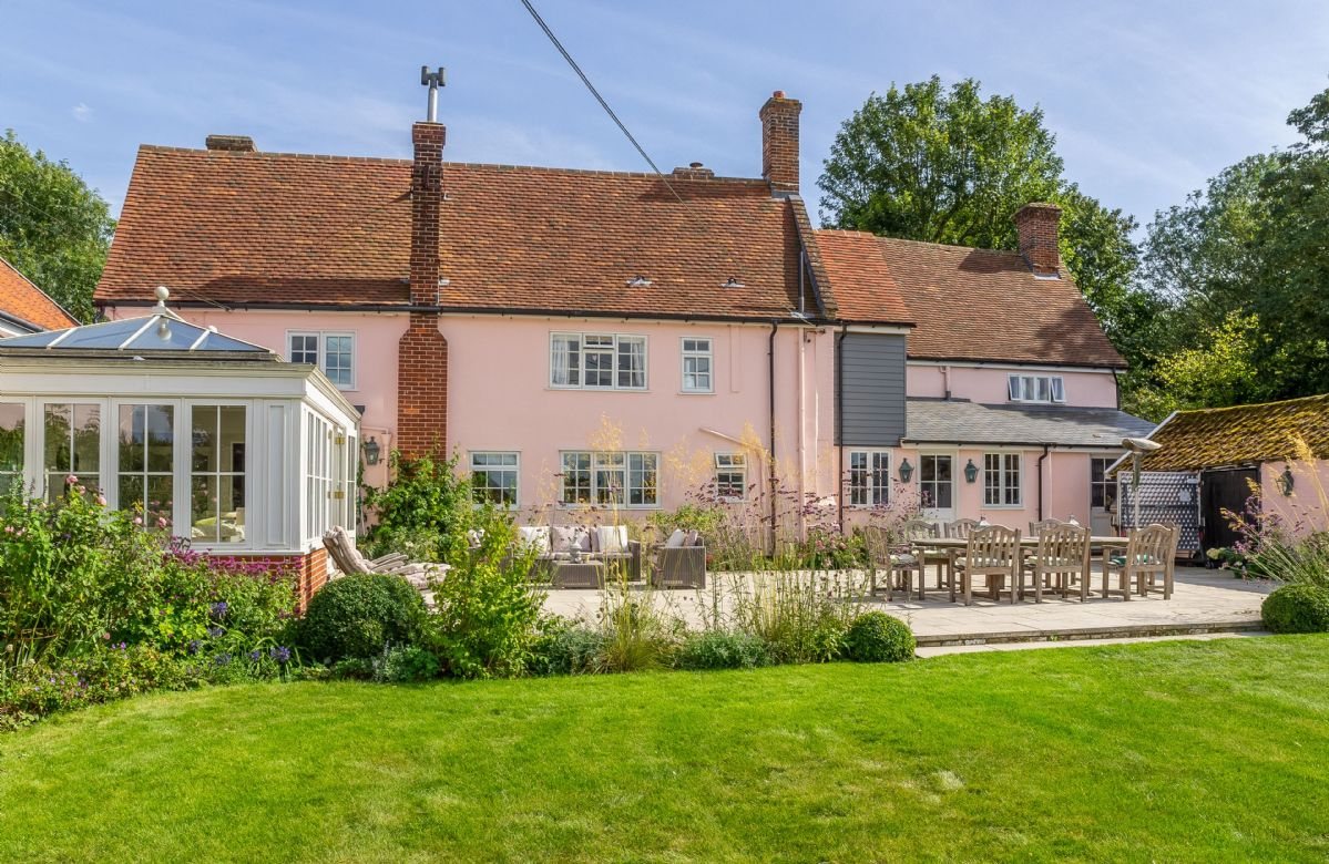The rear of the property with patio and garden furniture