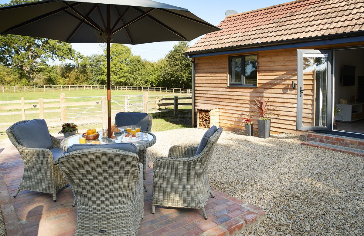Fully enclosed outdoor space with rattan garden furniture and barbecue