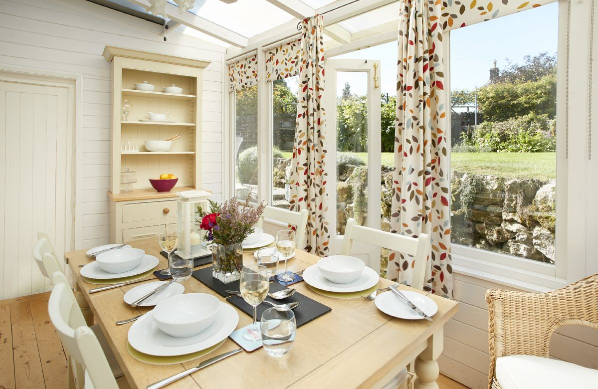 Ground floor: Dining room seating four guests overlooking the garden