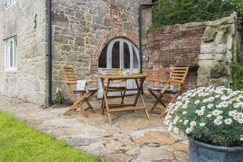 Patio area with a barbecue and garden furniture seating four guests