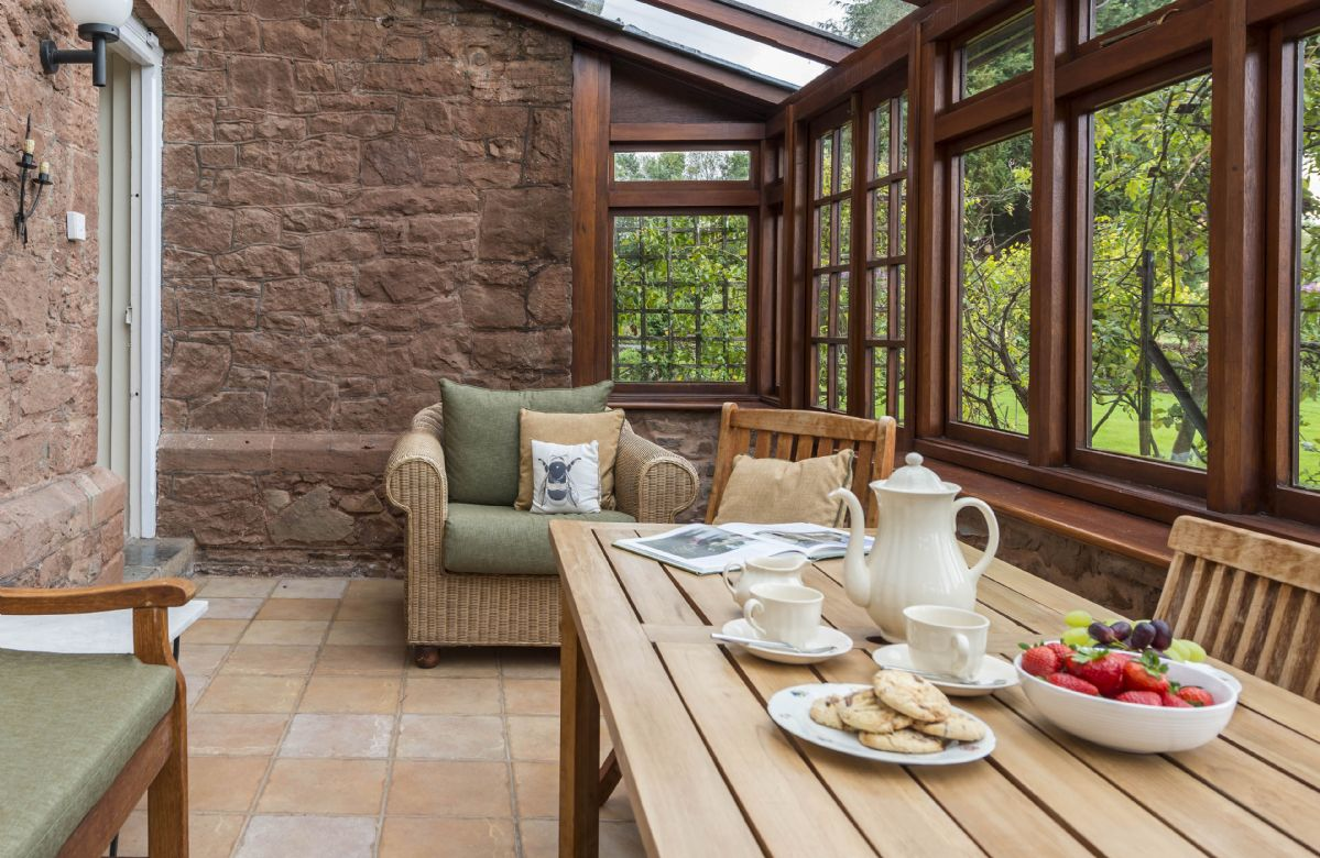 Ground floor: South facing conservatory with table seating six guests and doors to the garden
