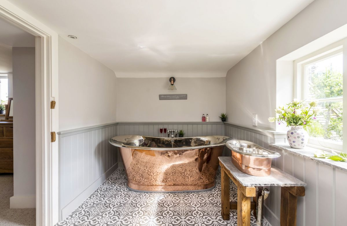 First floor: En-suite bathroom with copper bath and wash basin