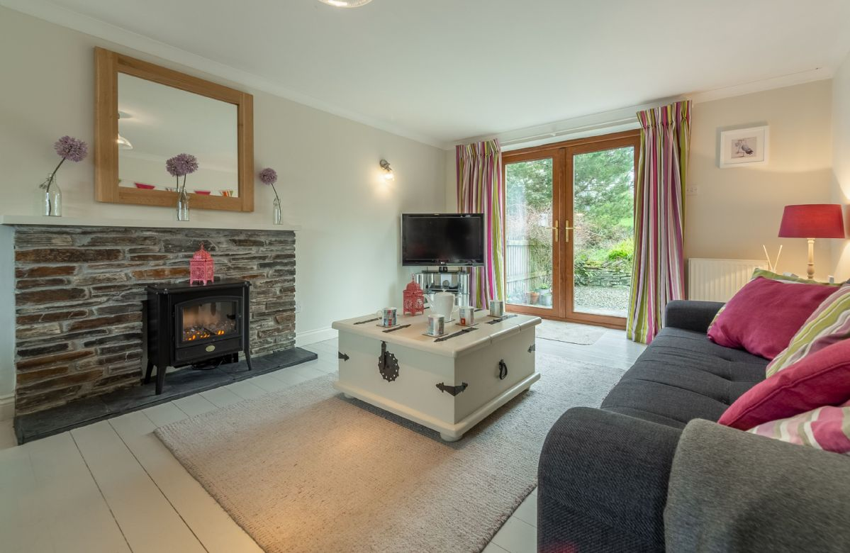 Ground floor: Comfortable sitting room with wood burner and french doors leading out to the patio
