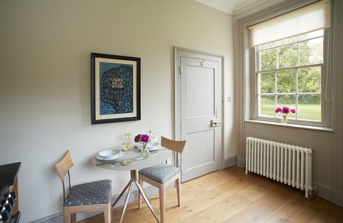 Ground floor: Small kitchen table seating two guests with views to the gardens