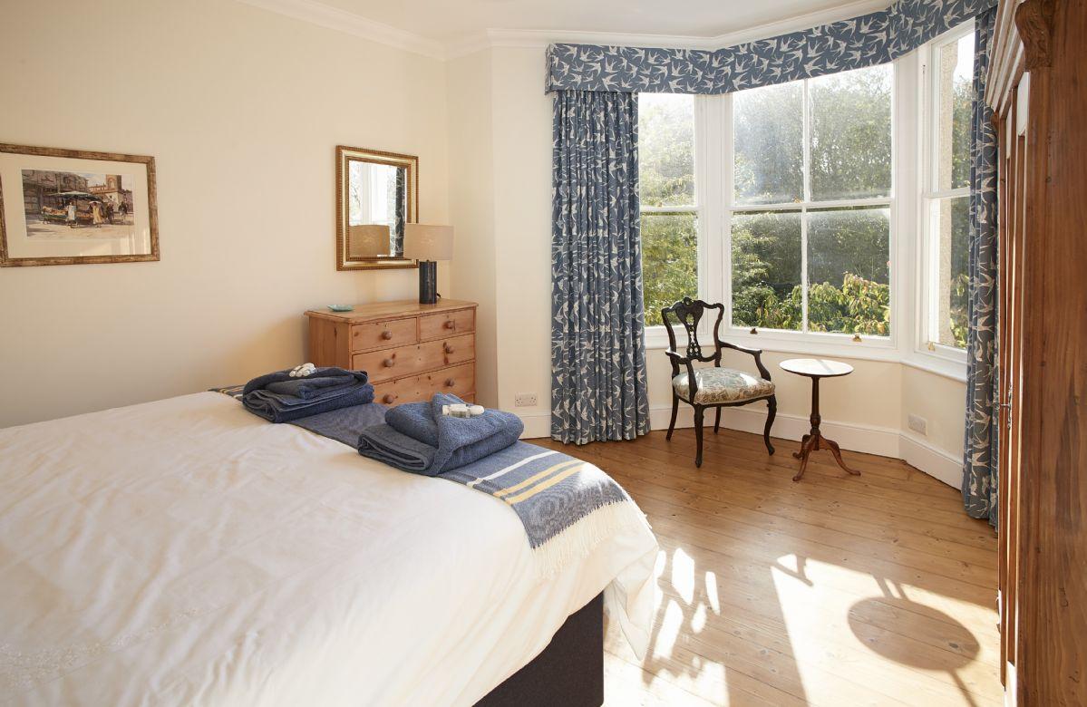 First floor: Bedroom with 6' super king zip and link beds and bay window overlooking the garden