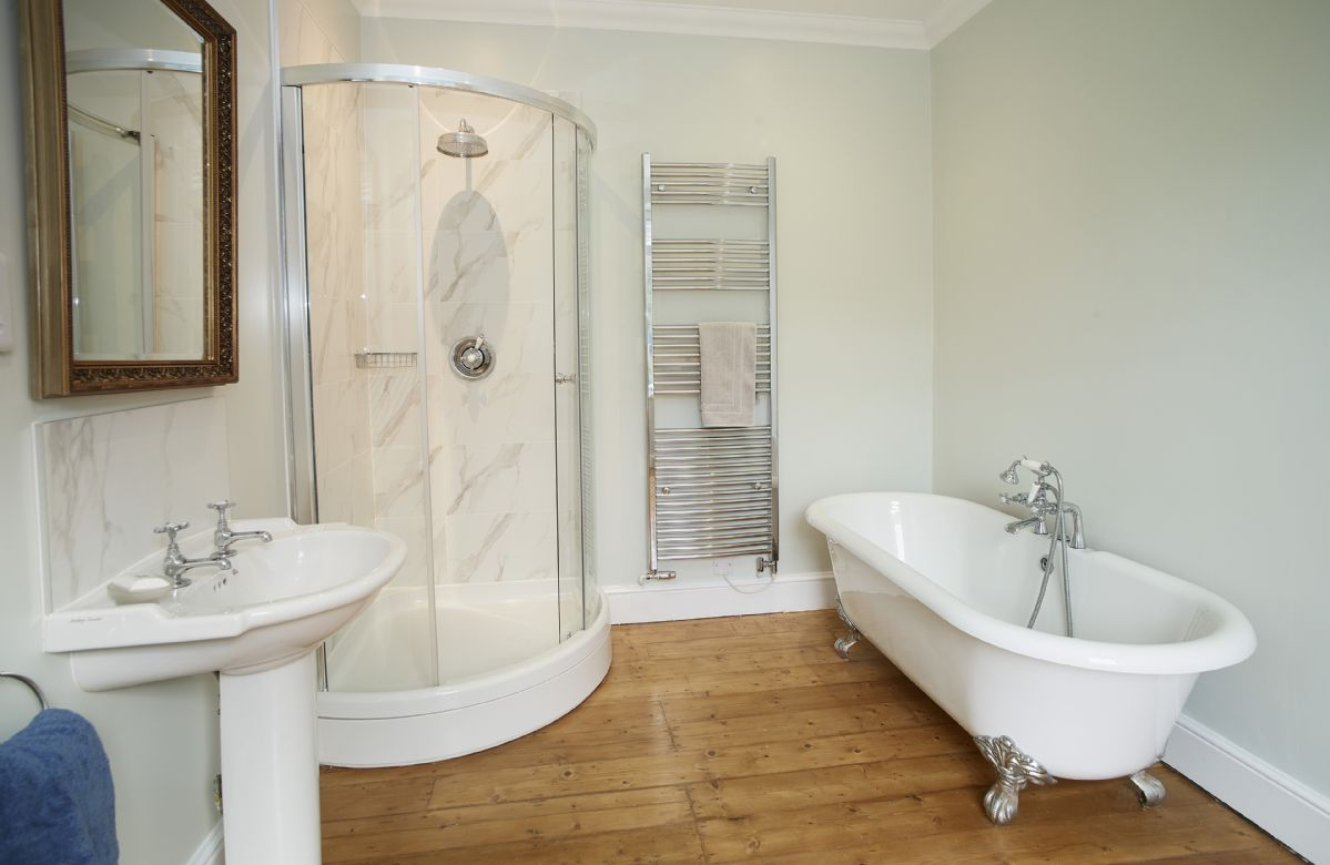First floor: Master en-suite bathroom with roll top bath and separate shower
