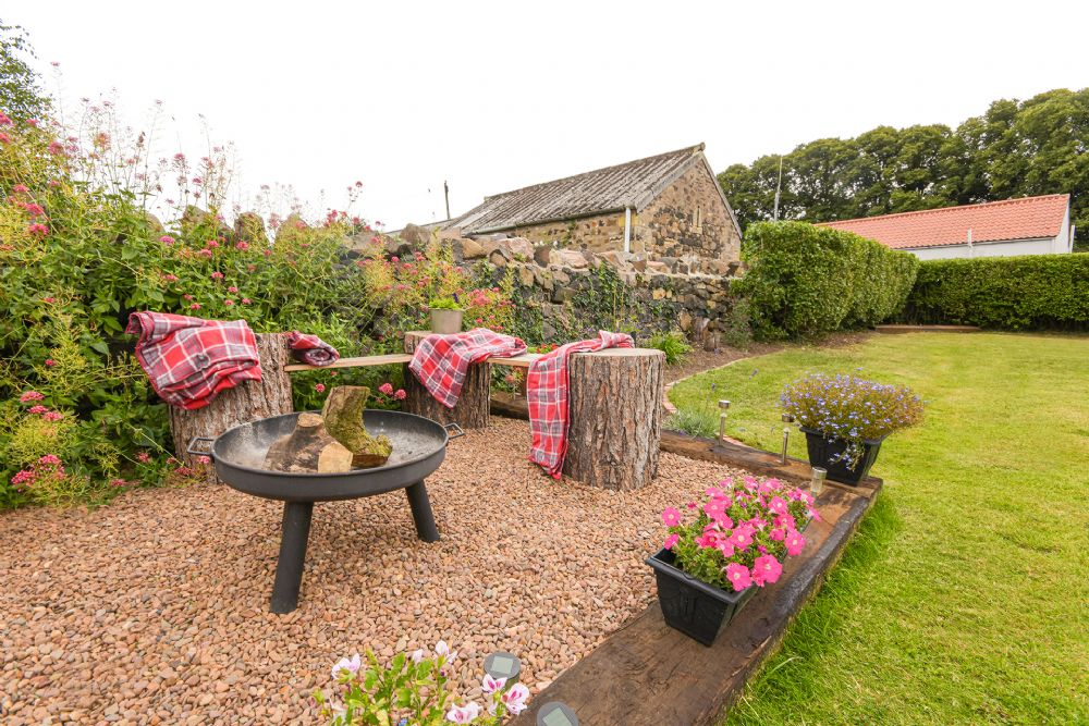 What an amazing garden; perfect to relax and eat outside in and the firepit and blankets for cold nights are a lovely touch!