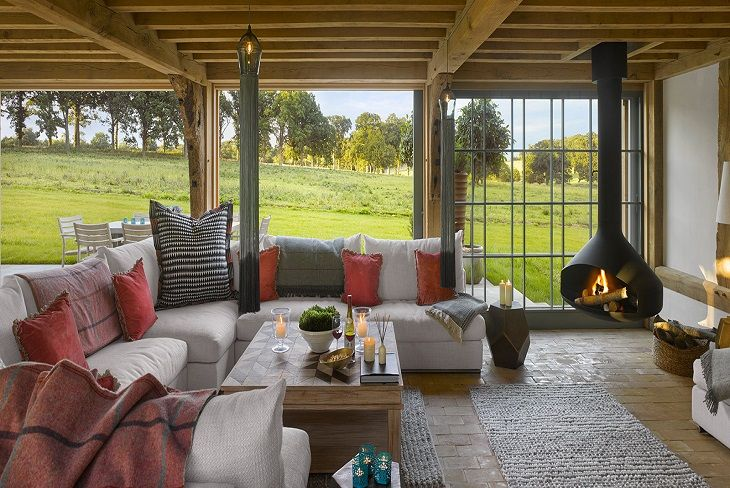 Ground floor:  The sitting room features an iconic Ergo Focus wood burner with sliding doors and timber screeens allowing the room to open up directly onto the farmyard and parkland