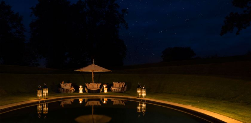 Outdoor swimming  pool with deck beds at night