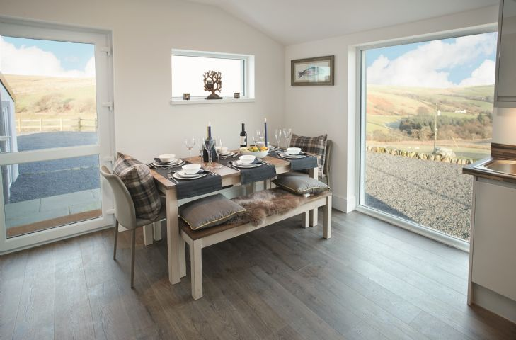 Ground floor: Open plan kitchen/dining area with underfloor heating and large floor to ceiling window overlooking the surrounding countryside