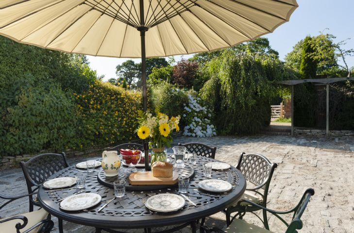 Lovely front cobbled courtyard with garden table and chairs, rattan sofa and pond (with safety grid)